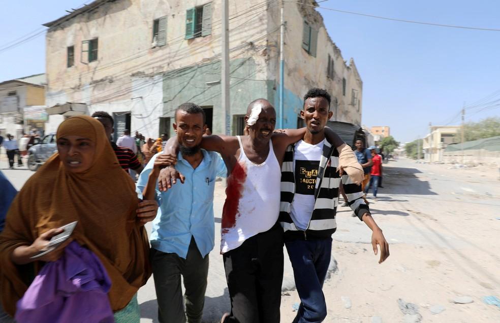 Civis ajudam homem ferido após explosão perto do palácio presidencial na Somália — Foto: Feisal Omar/Reuters