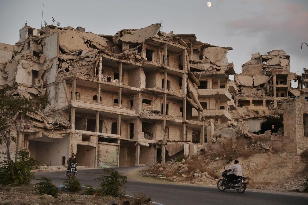 Foto de 20 de setembro de 2018 mostra motociclistas passando por edifícios destruídos na cidade de Ariha, na província de Idlib, na Síria — Foto: Ugur Can/DHA vía AP, arquivo