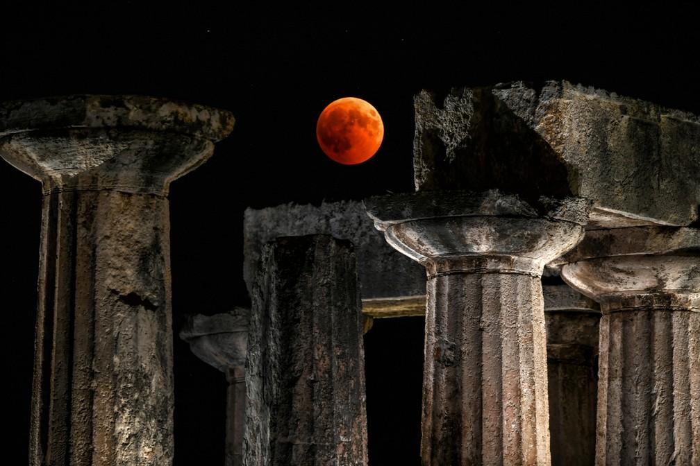 Eclipse da lua de sangue visto sobre as ruínas do templo de Apolo em Corinto, na Grécia. (Foto: Valerie Gache / AFP)