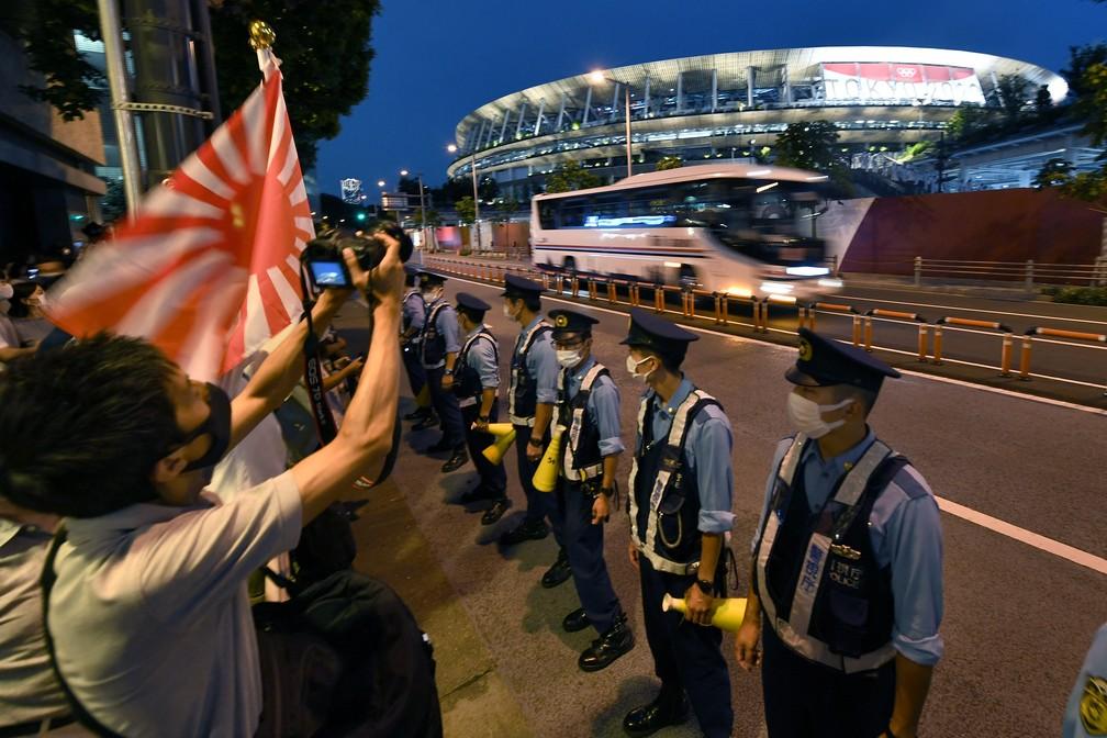 Policiais ficam em linha na frente de torcedores reunidos em frente ao Estádio Olímpico durante a cerimônia de abertura dos Jogos Olímpicos de Tóquio, no Japão — Foto: Kazuhiro Nogi/AFP