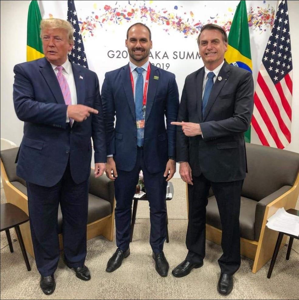 O deputado Eduardo Bolsonaro (PSL-SP) ao lado do pai, Jair Bolsonaro, e do presidente dos Estados Unidos, Donald Trump, durante cúpula do G20, no Japão  — Foto: Reprodução