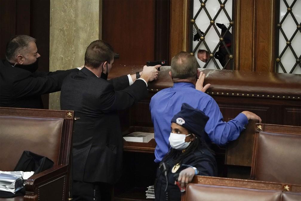 Policiais apontam armas para invasores que tentam adentrar o plenário da Câmara dos EUA, no Capitólio — Foto: J. Scott Applewhite/AP