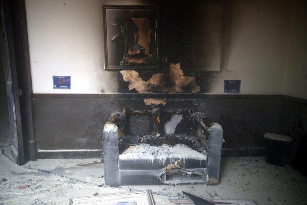 Sofá e quadro destruídos pelo fogo no Congresso da Guatemala neste sábado (21) — Foto: Moises Castillo/AP Photo