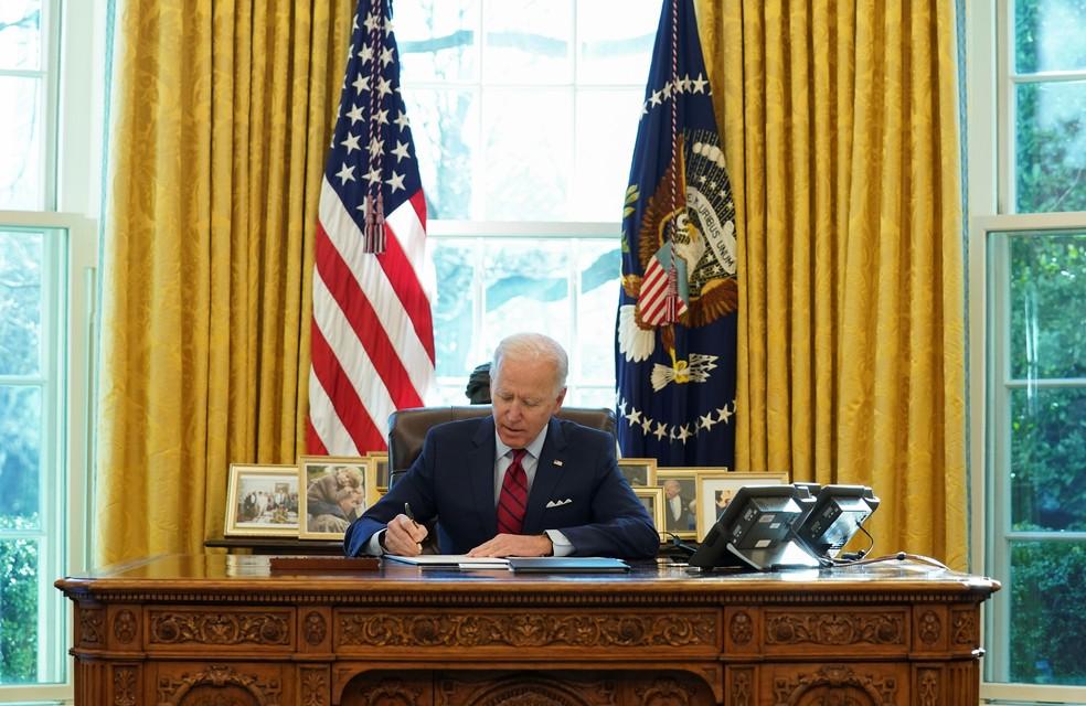 Joe Biden, presidente dos EUA, assina decretos na Casa Branca nesta quinta-feira (28) — Foto: Kevin Lamarque/Reuters