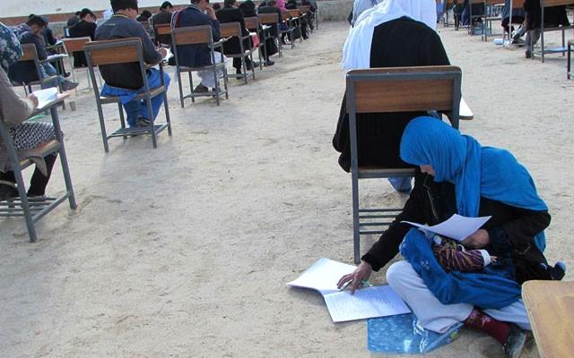 Jahan sentada no chão para acalmar a pequena Layla durante prova na universidade (Foto: Reprodução Facebook)