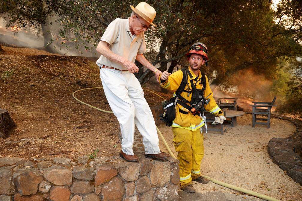 Bombeiro resgata morador de St, Helena, na Califórnia, durante incêndio neste domingo (27) — Foto: Stephen Lam/Reuters