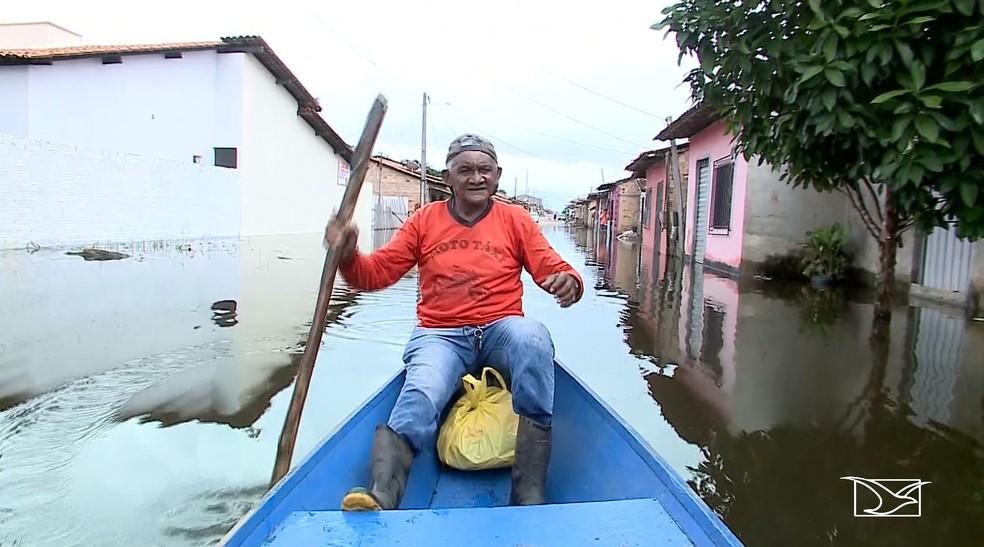 Mototaxista Raimundo Guedes usa canoa para vigiar o que sobrou na casa dele em Santa Helena — Foto: Reprodução/TV Mirante