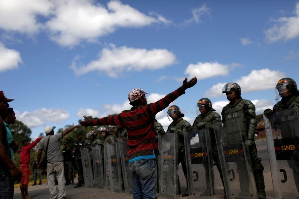 Grupo na frente de soldados venezuelanos na fronteira com o Brasil em Pacaraima — Foto: REUTERS/Ricardo Moraes