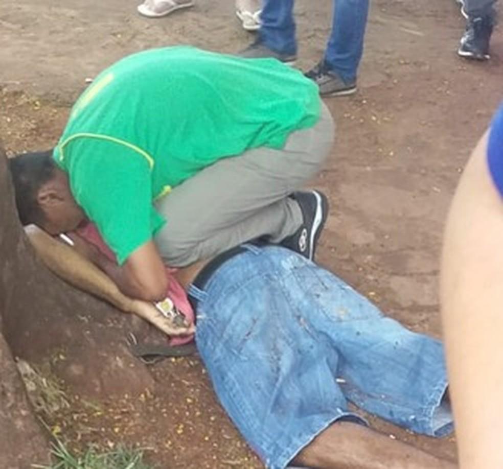 Adolescente chora sobre corpo de pai, que foi executado com tiros de fuzil e pistola, em Pedro Juan Caballero, Paraguai. — Foto: Léo Veras/Porã News
