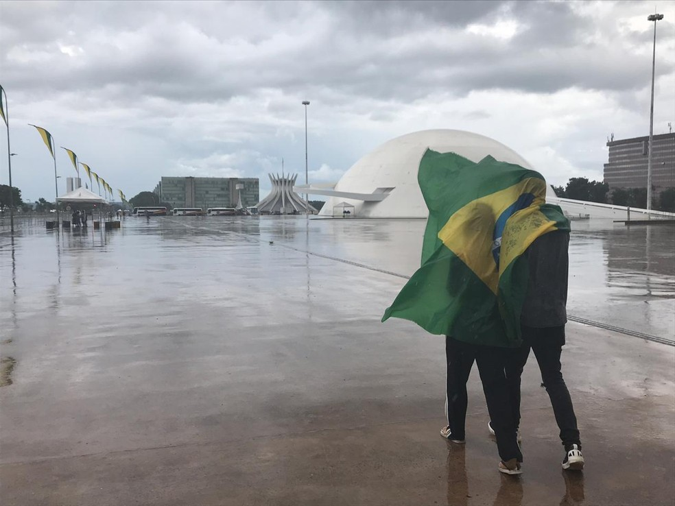 Helen e Marcos usam a bandeira do Brasil para se proteger da chuva na Esplanada dos Ministérios — Foto: Marília Marques/G1