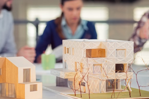 Team of young architects working on a home project in the studio, model houses in front. (Foto: Getty Images)