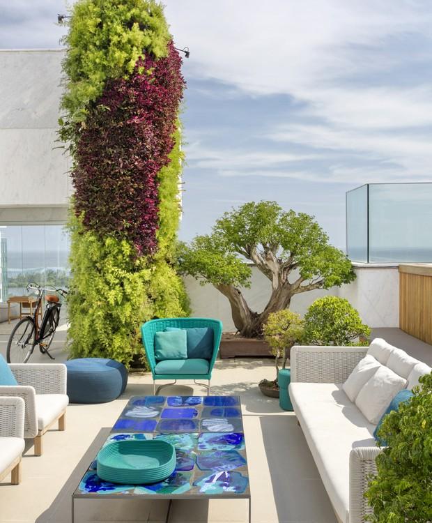 O mix de cores do jardim vertical acontece pela combinação de  xanadu, aspargos, bromélias e trapoeraba, entre outras. O bonsai gigante vem do antigo endereço da família, que também tinha o paisagismo assinado por Carmen Mouro (Foto: Juliano Colodetti/MCA Estúdio/Divulgação )