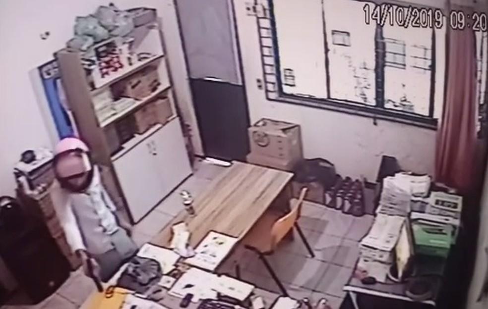 Suspeito ameaça funcionário para que ele entregue os envelopes com dinheiro — Foto: Reprodução