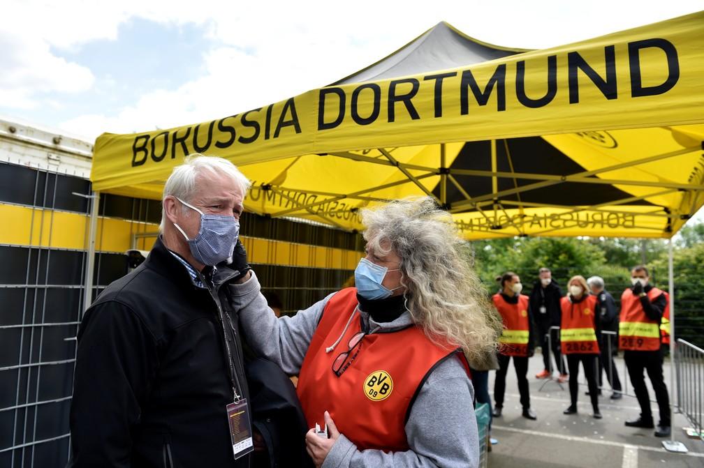 Funcionária mede a temperatura de membro de equipe de transmissão de Borussia Dortmund x Schalke 04 — Foto: Reuters