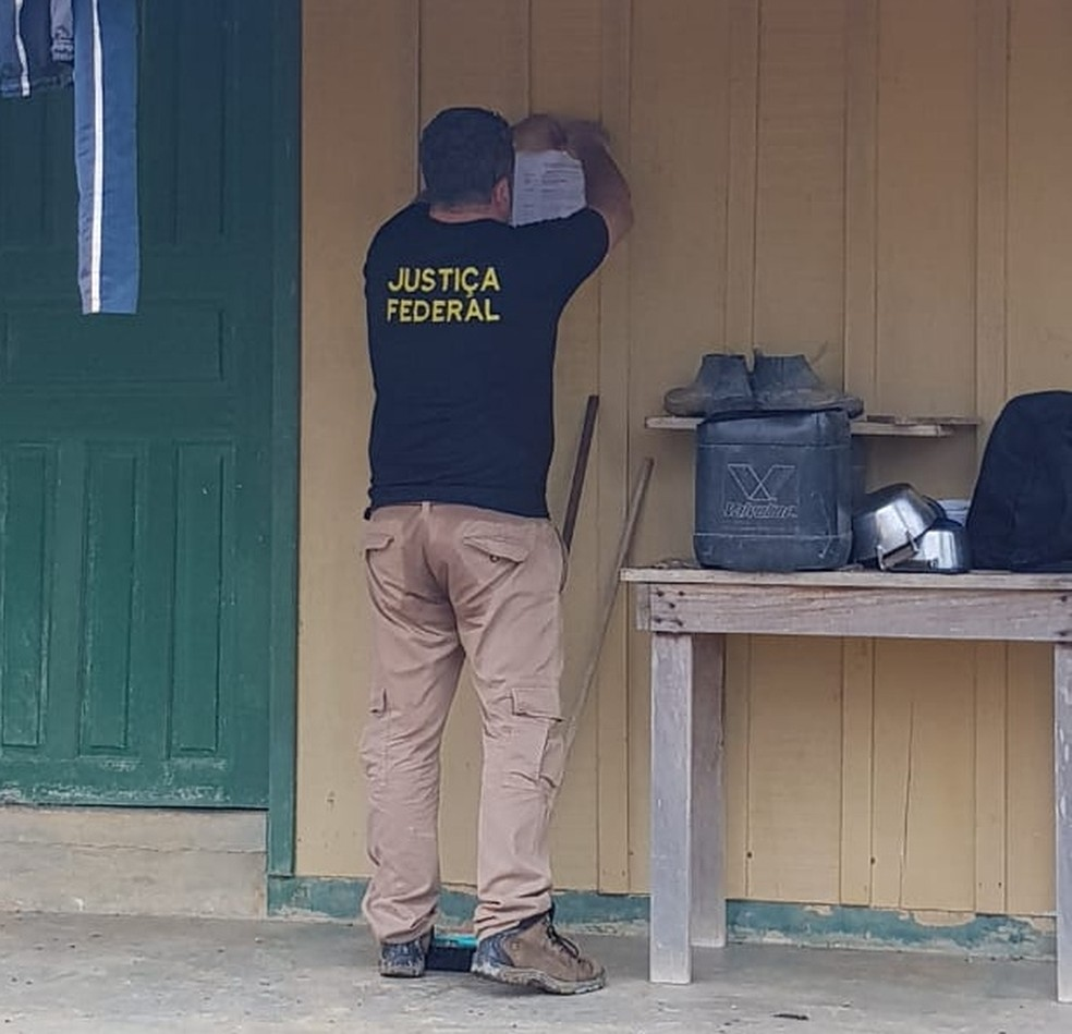 Agente da Justiça Federal fixa intimação de desocupação em benfeitoria ilegal construída na TI Kawahiva do Rio Pardo — Foto: Funai/Assessoria