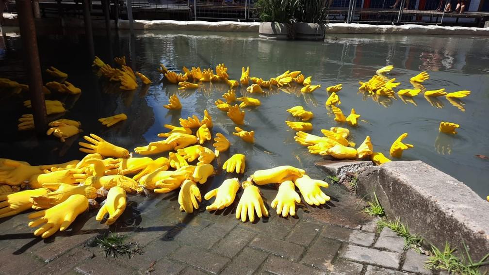 Luvas parte de instalação do artista Jandr Reis, em área alagada em frente à praça do Relógio, no Centro de Manaus — Foto: Meike Farias/Rede Amazônica