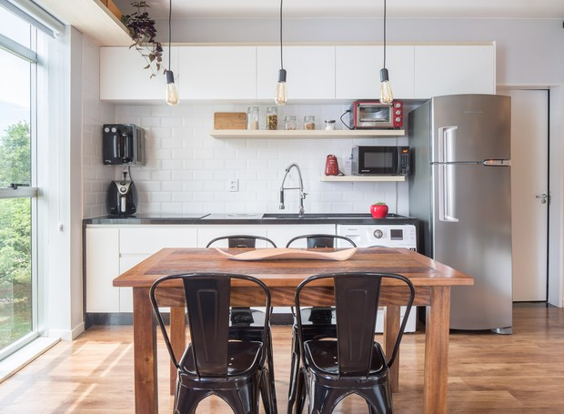 A marcenaria da cozinha, branca, reflete a claridade abundante pelo apartamento. Prateleiras deixam a bancada livre e multiplicam a área para os eletrodomésticos. Execução da Caminho Oficina (Foto: Joana França/Divulgação)