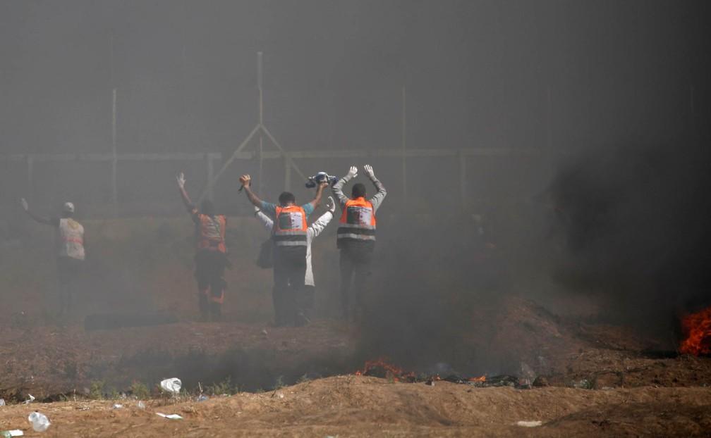 Paramédicos palestinos erguem os braços em meio à fumaça sinalizando que estão apenas recolhendo mortos e feridos na fronteira entre Gaza e Israel, em conflito após protestos contra a inauguração da embaixada dos EUA em Jerusalém (Foto: Thomas Coex/AFP)