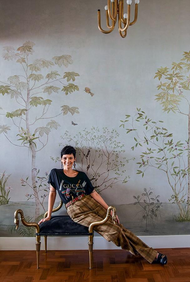 Papel de parede da Branco, lustre da Dominici e cadeira comprada de uma amiga compõem a entrada do apê. Camiseta, calça, brincos, cinto e sapatos, tudo Gucci (Foto: Romulo Fialdini)