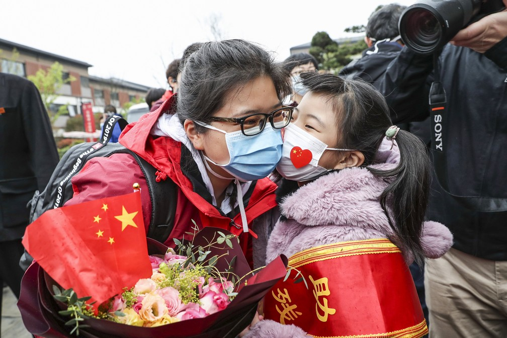 31 de março: na foto, integrante de uma equipe médica de combate à Covid-19 em Wuhan, na província de Hubei, epicentro da doença na China, é recebida pela filha na volta para casa em Huaian, na província de Jiangsu. — Foto: STR / AFP