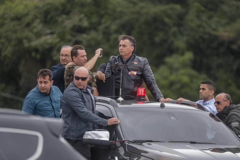 Bolsonaro é transportado em caçamba de caminhonete antes de seguir passeio de moto em Florianópolis — Foto: Tiago Ghizoni/NSC