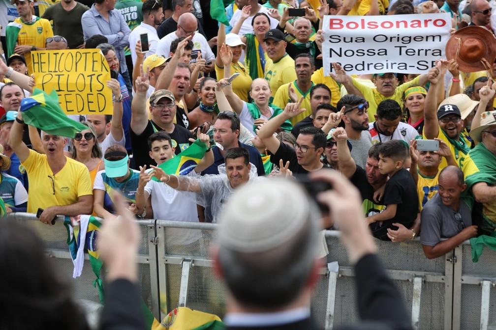 Um grupo de jornalistas israelenses é saudado efusivamente pelo público próximo à grade, com gritos de 'Israel' e 'Jerusalém', ao chegar à área de imprensa na Praça dos Três Poderes — Foto: Fábio Tito/G1