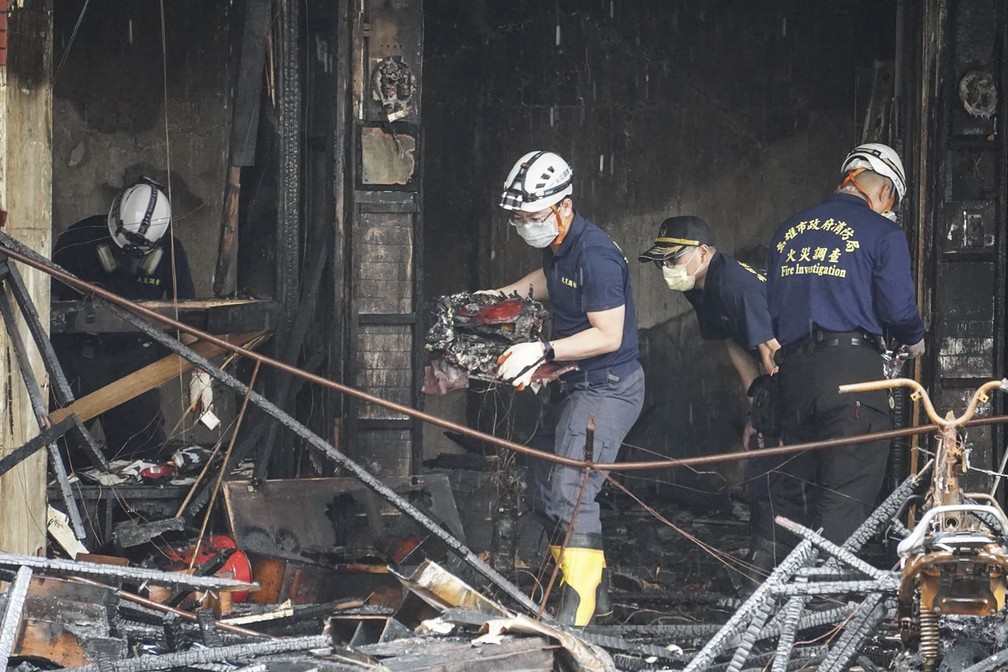 Equipes de emergência trabalham em prédio que pegou fogo na cidade de Kaohsiung, no sul de Taiwan, e deixou dezenas de mortos e feridos em 14 de outubro de 2021 — Foto: CNA (Agência Central de Notícias de Taiwan) via AFP