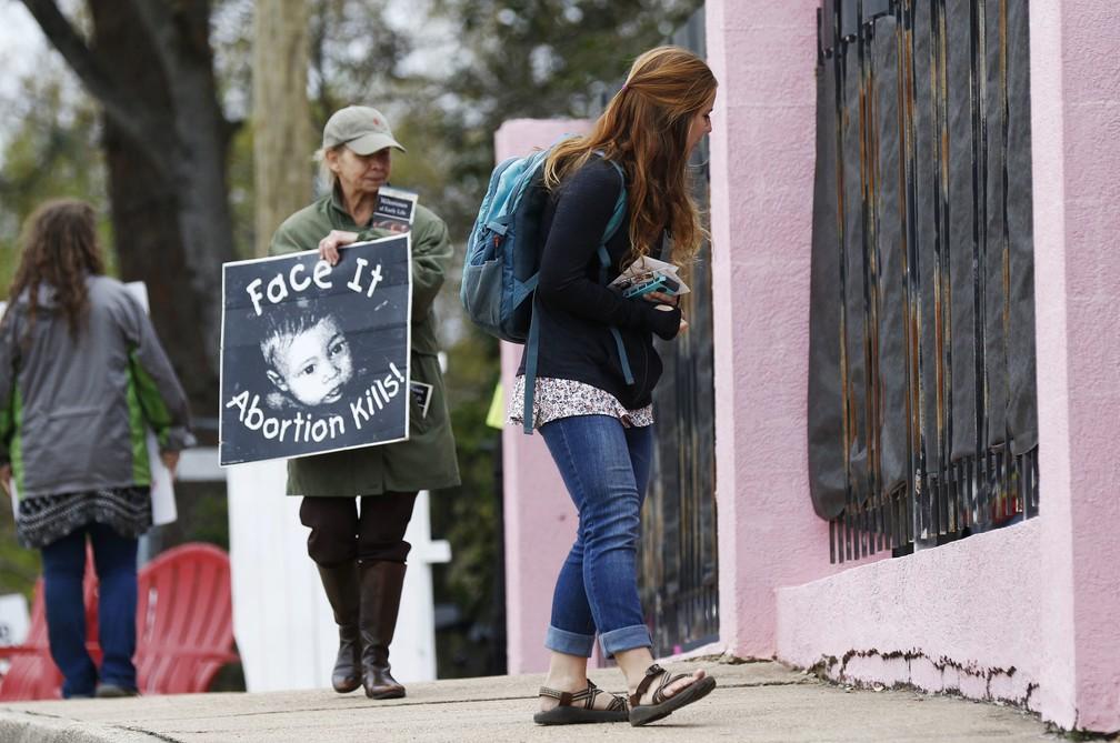 """Mulher segura um cartaz que diz """"encare: o aborto mata!"""" na porta da clínica Jackson Women's Health Organization, única clínica a fazer abortos no Mississippi, no dia 20 de março de 2018. — Foto: Rogelio V. Solis/AP"""