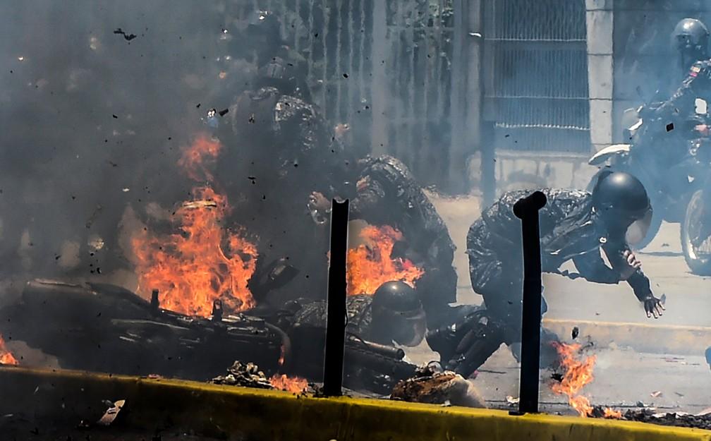 Policiais se afastam do fogo após explosão de motos em protesto na Venezuela (Foto: Juan Barreto/AFP)