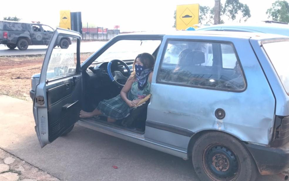 Família com grávida dorme dentro de carro em frente à sede da força-tarefa em Cocalzinho de Goiás  — Foto: Vitor Santana/G1