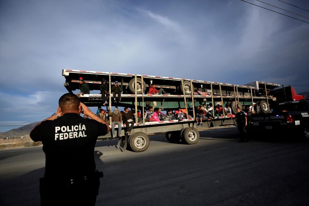 Um policial tira fotos de migrantes na carroceria de um caminhão em Saltillo, no México, onde ficarão em um abrigo temporário enquanto seguem em jornada para os EUA — Foto: Daniel Becerril/Reuters