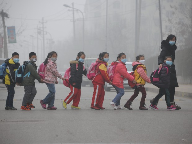 Crianças usando máscaras contra poluição atravessam a rua em Jinan, na província de Shandong, na China, nesta quinta-feira (24) (Foto: AFP)