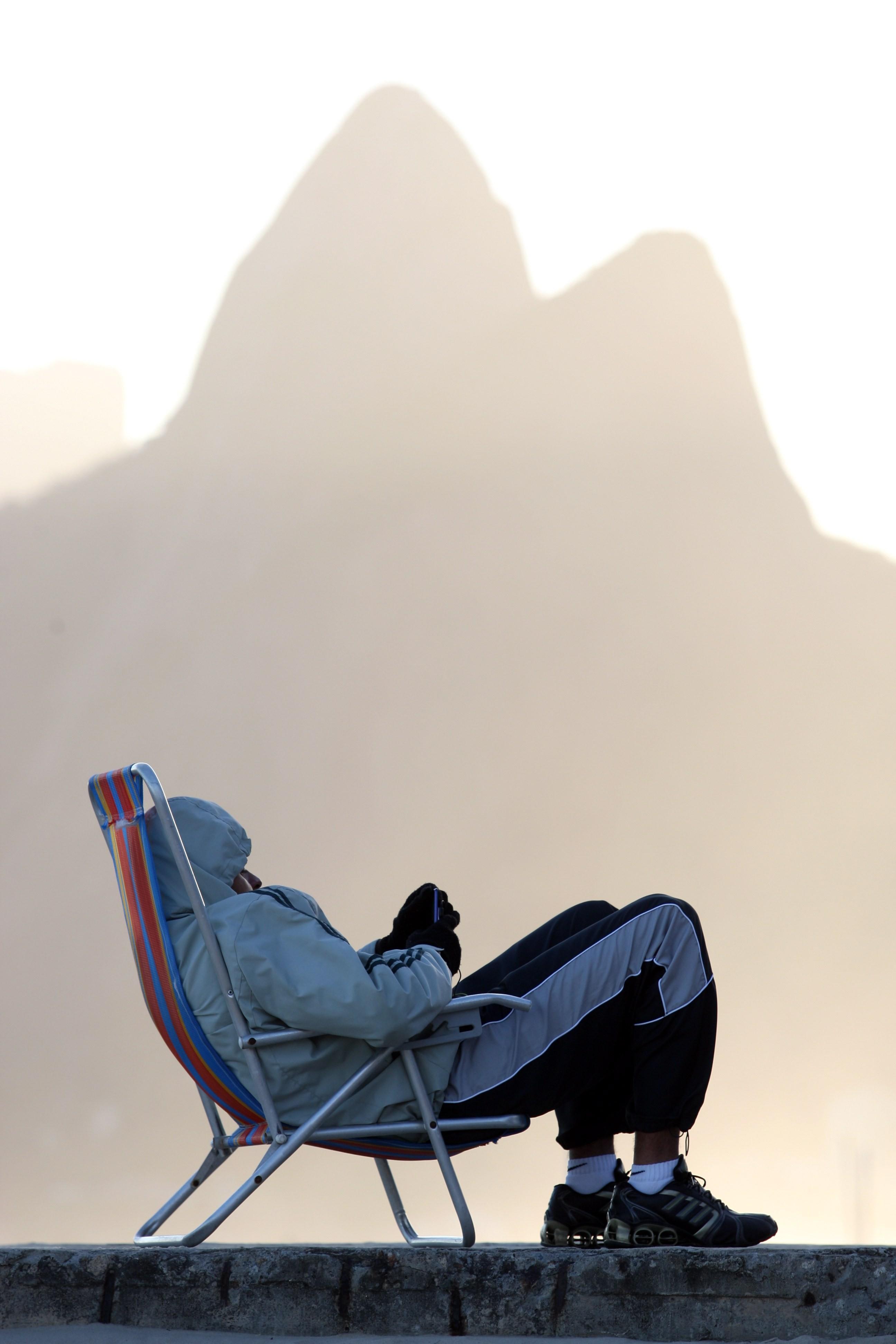 Homem repousa todo encasacado em cadeira de praia, com o Morro Dois Irmãos ao fundo