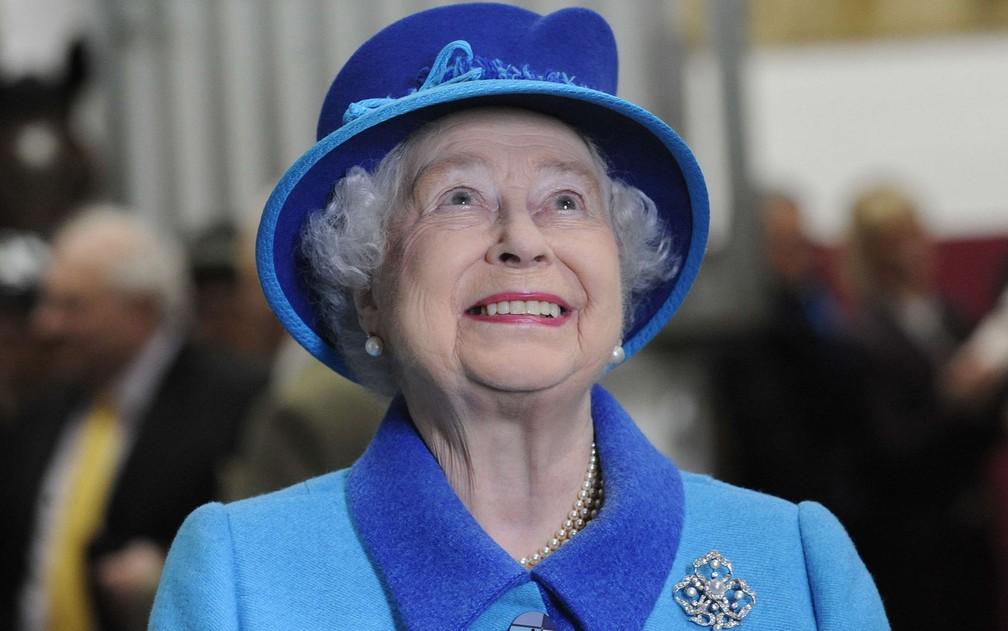 A rainha Elizabeth checa o pedigree do vencedor do concurso 'Royal Ascot Gold Cup' durante visita ao País de Gales, em 2014. — Foto: Rebecca Naden/Reuters