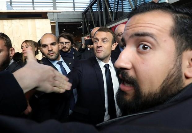 Benalla aparece em primeiro plano em foto de fevereiro, com Macron ao fundo (de gravata preta); 'senhor segurança' foi demitido em 20 de julho (Foto: Reuters via BBC)