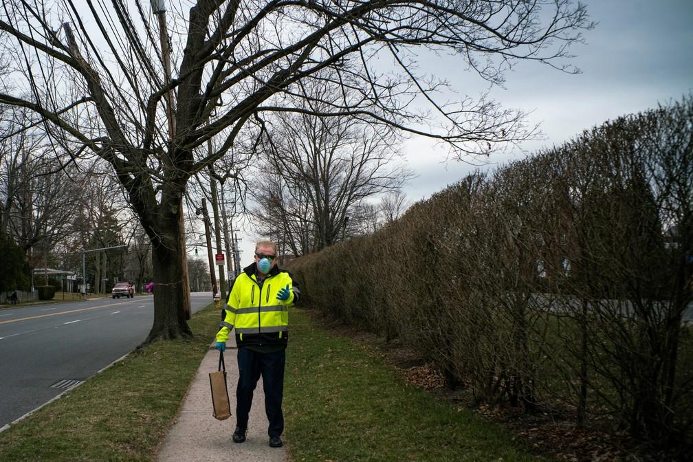 Homem usa máscara ao caminhar perto de sinagoga em New Rochelle, subúrbio de Nova York fechado nesta terça-feira (10) por novo coronavírus — Foto: Eduardo Munoz/Reuters