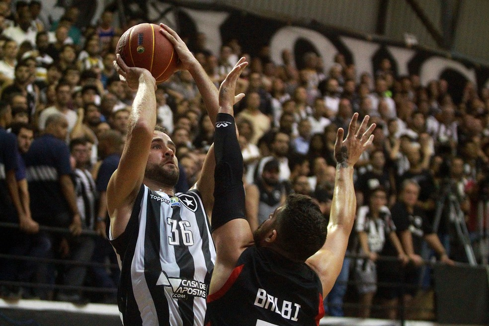Arthur tenta o arremesso marcado de perto pelo argentino Balbi — Foto: Vitor Silva/Botafogo