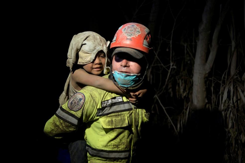 Criança coberta de cinzas é socorrida em El Rodeo, após a erupção de vulcão de Fogo, na Guatemala, no domingo (3)  (Foto: Fabricio Alonzo/ Reuters)