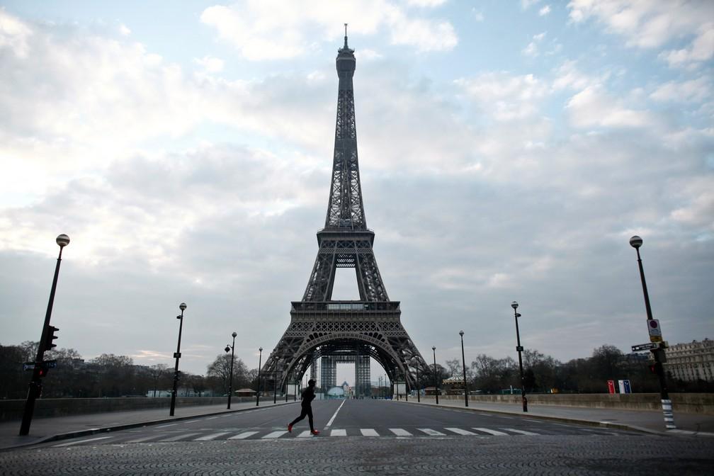 18 de março - Um homem corre em frente à Torre Eiffel, em Paris, completamente vazia após o presidente francês Emmanuel Macron anunciar que a partir do meio-dia da terça-feira (17) as pessoas poderão deixar o local onde vivem apenas para as atividades necessárias, como como comprar comida, ir trabalhar ou fazer caminhadas devido à epidemia do novo coronavírus (COVID-19) — Foto: Thibault Camus/AP