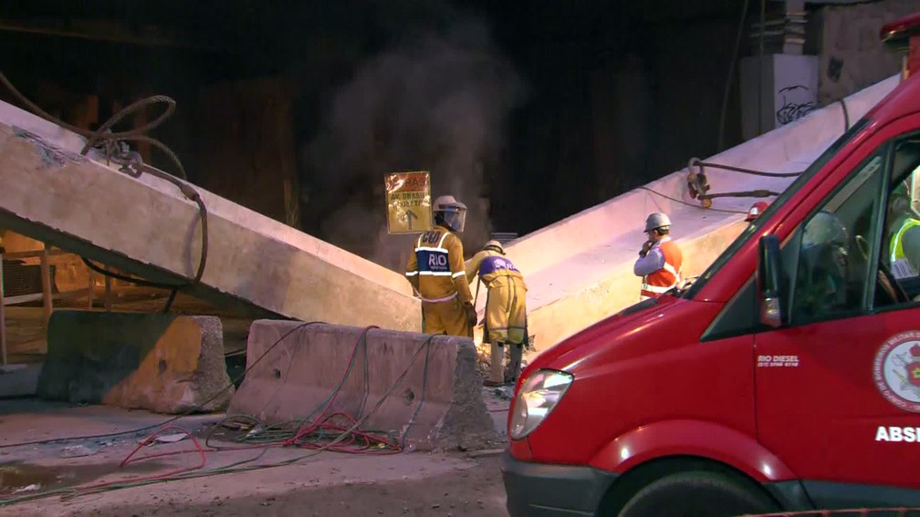 Operários serram viga que desabou na Avenida Brasil — Foto: Reprodução/TV Globo