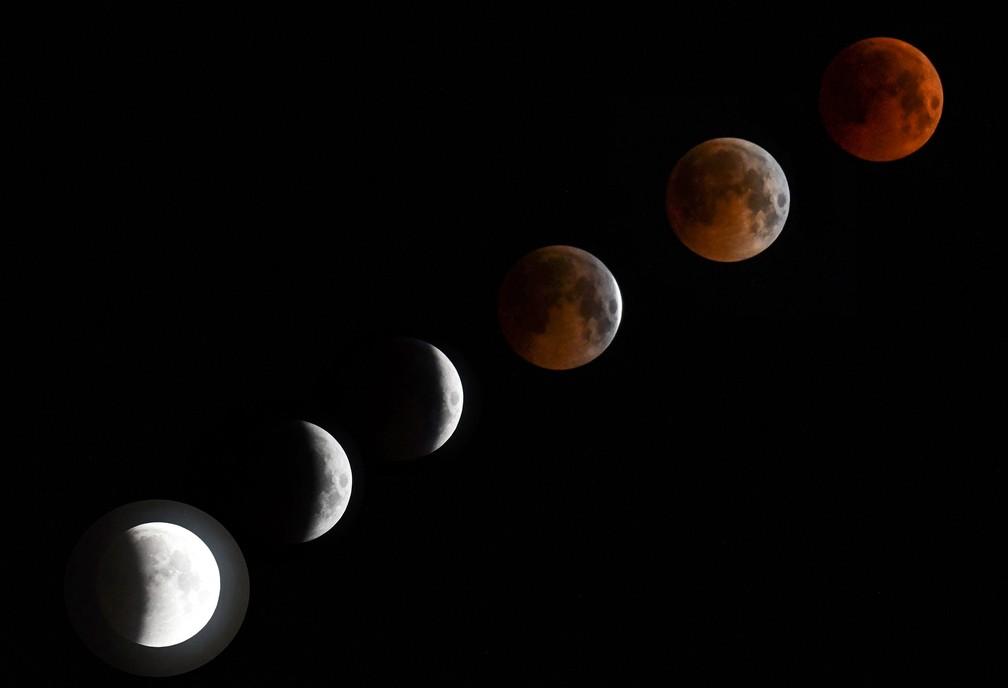 Montagem com seis fotos mostra a evolução do eclipse parcial ao total com Lua de Sangue de 2018 — Foto: Vyacheslav Oseledko/AFP