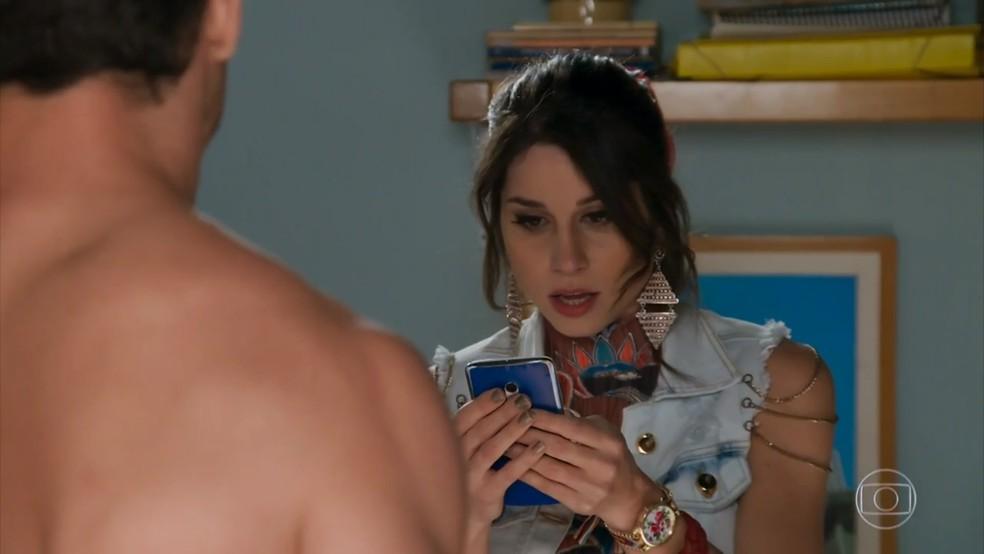 Carmela (Chandelly Braz) vê mensagem de Apolo (Malvino Salvador) no celular de Adônis (José Loreto) - 'Haja Coração' — Foto: Globo