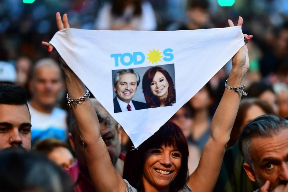 Manifestante mostra lenço com fotos de Alberto Fernández e Cristina Kirchner neste domingo (27) dia de eleições na Argentina — Foto: Ronaldo Schemidt/AFP