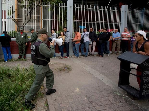 Soldado usa um megafone para orientar eleitores que fazem fila para votar em Caracas, no domingo (6) (Foto: AP Photo/Fernando Llano)