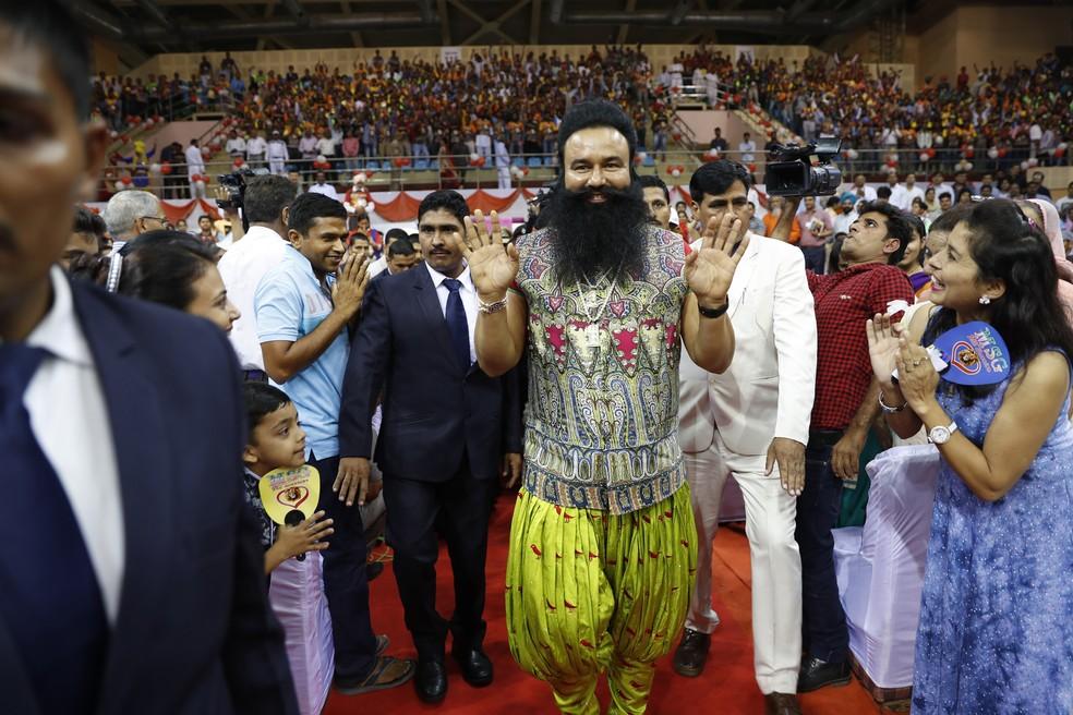 Em foto de 2015, Gurmeet Ram Rahim Singh (ao centro) cumprimenta seguidores durante lançamento de filme na Índia (Foto: AP Photo/Tsering Topgyal, File)