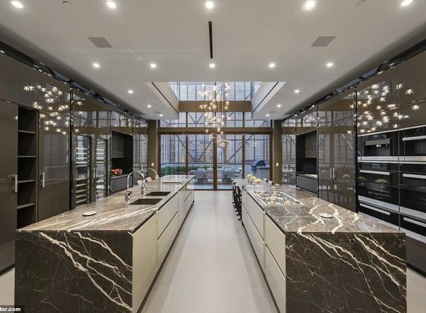 A cozinha é ampla e moderna, com superfícies espelhadas e a bancada de mármore (Foto: Realtor/ Reprodução)