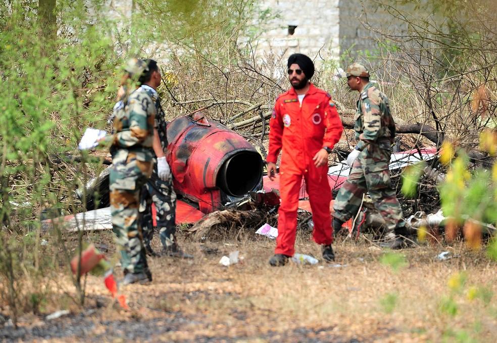 Soldados isolam área ao redor dos destroços de duas aeronaves do Time de Exibição Aerobática Surya Kiran, da Força Aérea da Índia, que colidiram no ar e caíram durante ensaio na Estação da Força Aérea de Yelahanka, em Bengaluru. Dos 3 pilotos a bordo dos aviões, 1 morreu e 2 conseguiram ejetar-se em segurança. Eles faziam um treinamento preparando-se para o evento Aero India — Foto: Reuters/Stringer