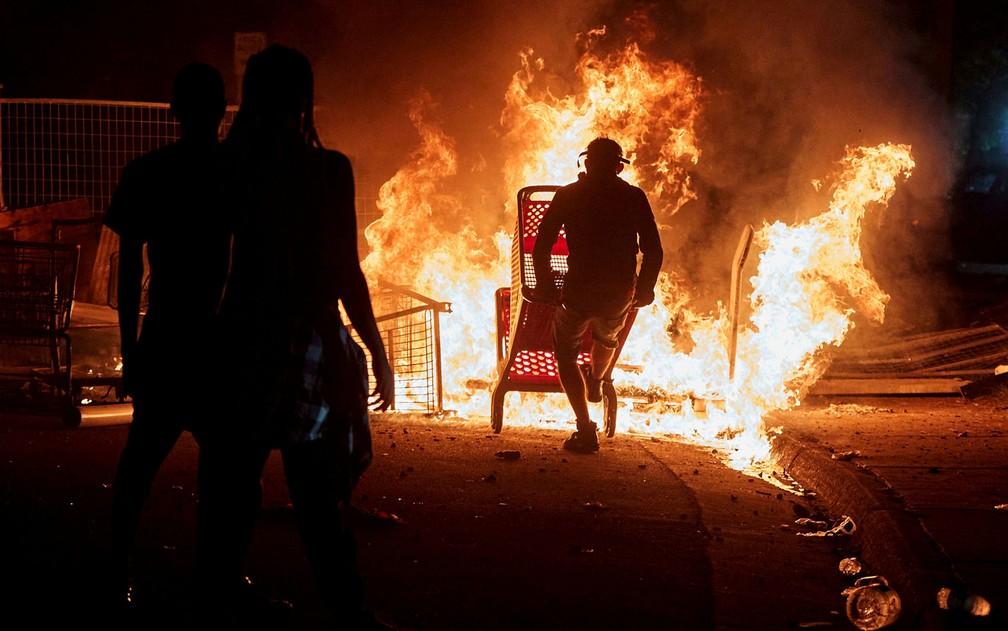 Manifestantes observam carrinhos de compra queimando perto de delegacia de polícia em Minneapolis, durante protesto pela morte de George Floyd, na noite de quarta-feira (27) — Foto: Reuters/Adam Bettcher