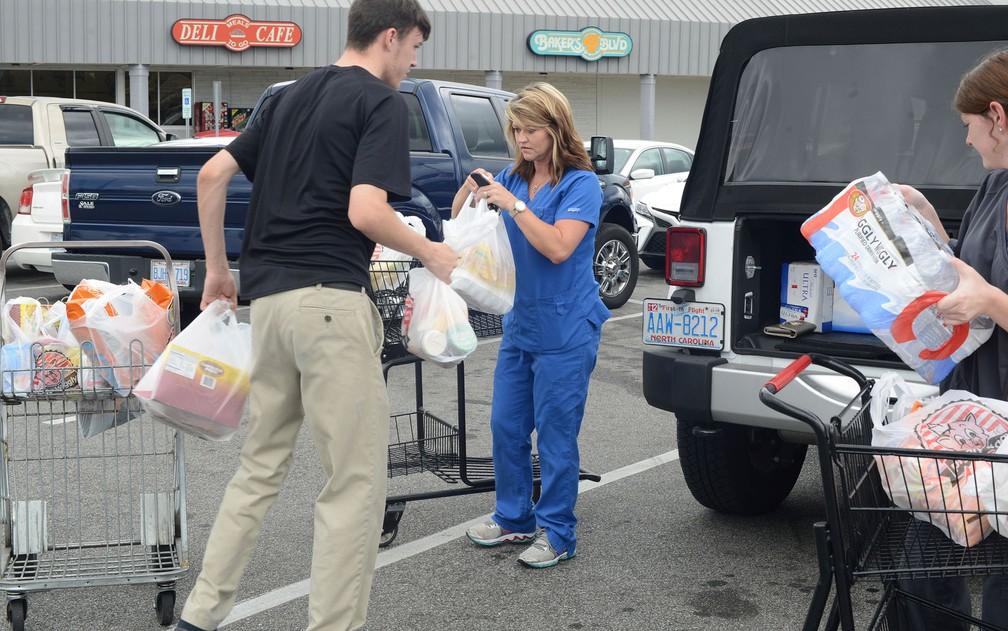 Pessoas carregam compras para estocar alimentos e água para a passagem do furacão Florence, na segunda-feira (10) (Foto: Janet S. Carter/Daily Free Press via AP)