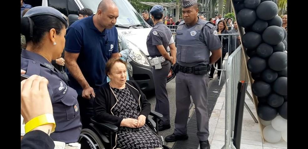 Maria do Céu, mãe de Gugu, chega de cadeira rodas para velório do filho nesta sexta (29) na Alesp — Foto: Marília Neves/G1